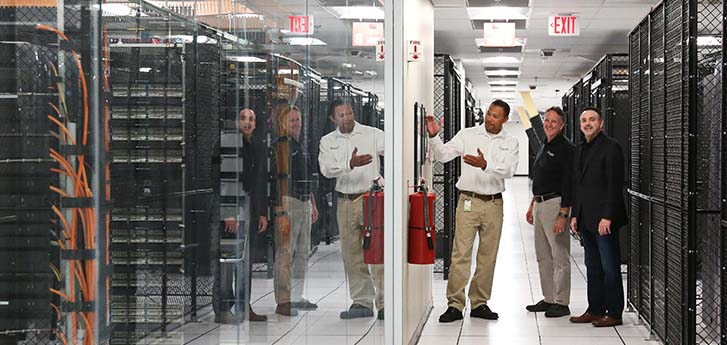Three men walking through data center looking at server racks