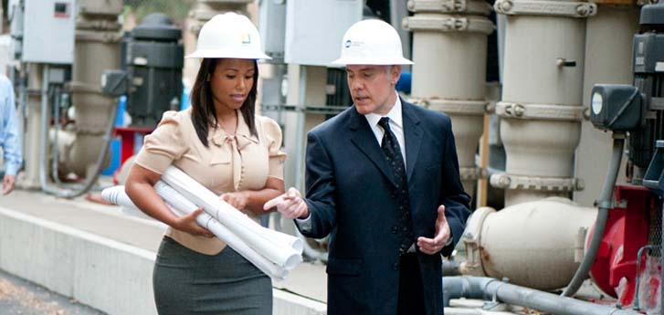 Male and female on site at a power plant wearing white construction hats