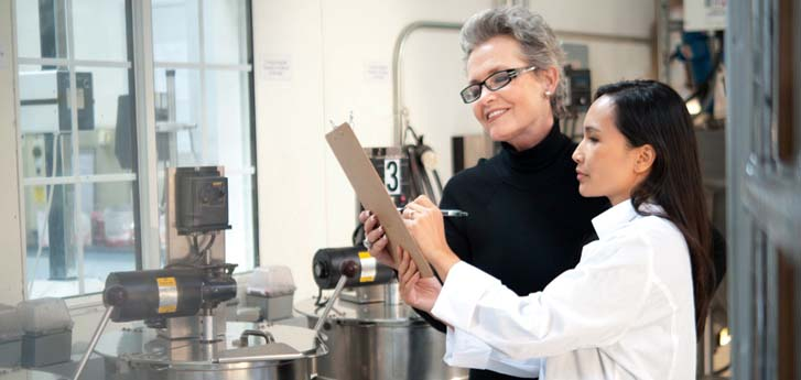 woman and lab technician in cosmetic plant