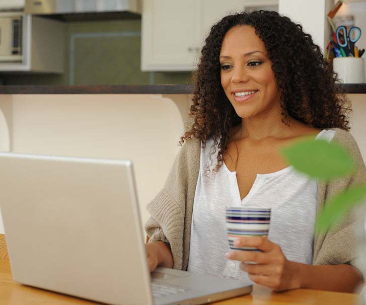 Woman holding a cup of coffee, while using a laptop