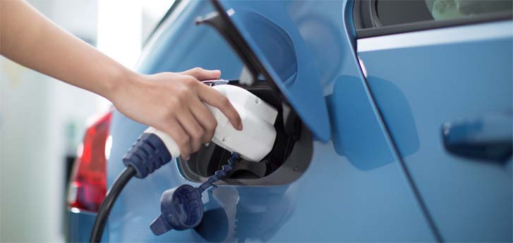 Hand holding electric vehicle pump inserted into car