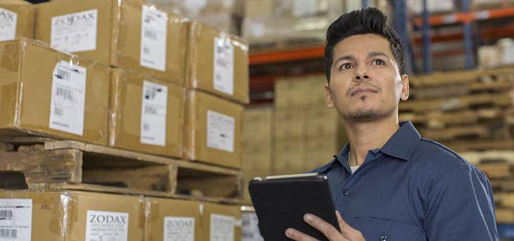 Man with tablet inside a warehouse checking inventory
