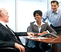 Two men and a woman smiling and having a discussion at work