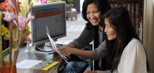 Two women looking at a piece of document while in front of a computer screen