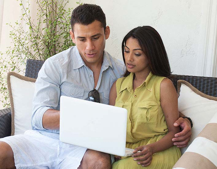 Couple sitting down looking at the laptop