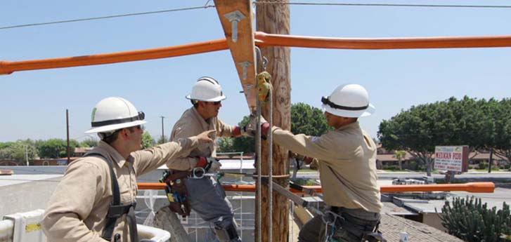 Three SCE service men in hard hats fixing a pole