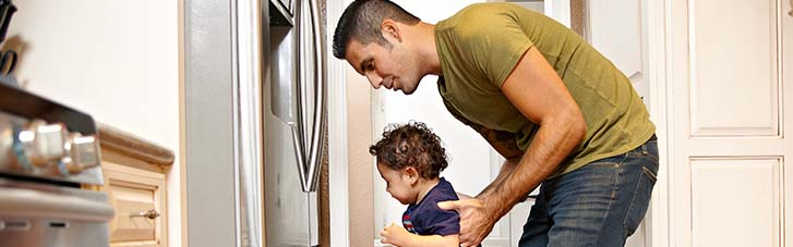 Father and son in front of a refrigerator