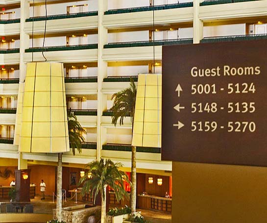 Image of hotel hallway overlooking open hotel lobby with a guest room directional sign