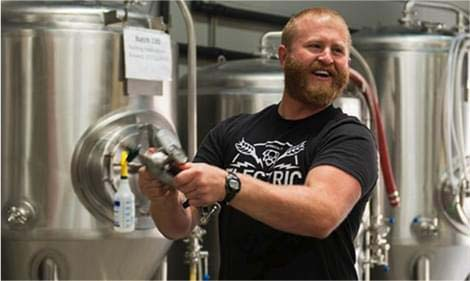 "A man in a tee-shirt that reads ""electric"" checks large vats in a brewery"